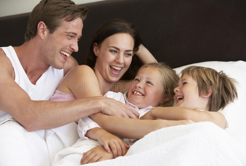 Jeune famille ayant l'amusement dans le lit photos stock