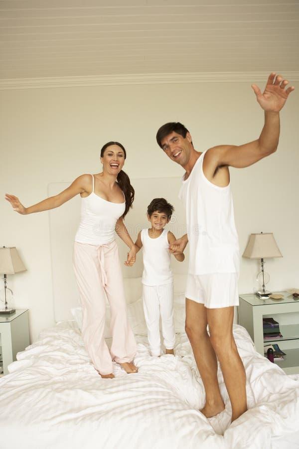 Jeune famille ayant l'amusement rebondissant sur le lit images stock