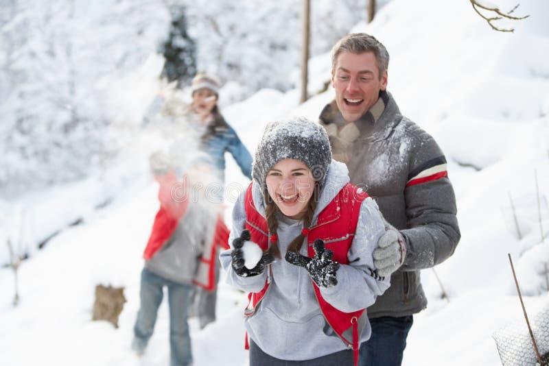 Jeune famille ayant le combat de boule de neige photo stock