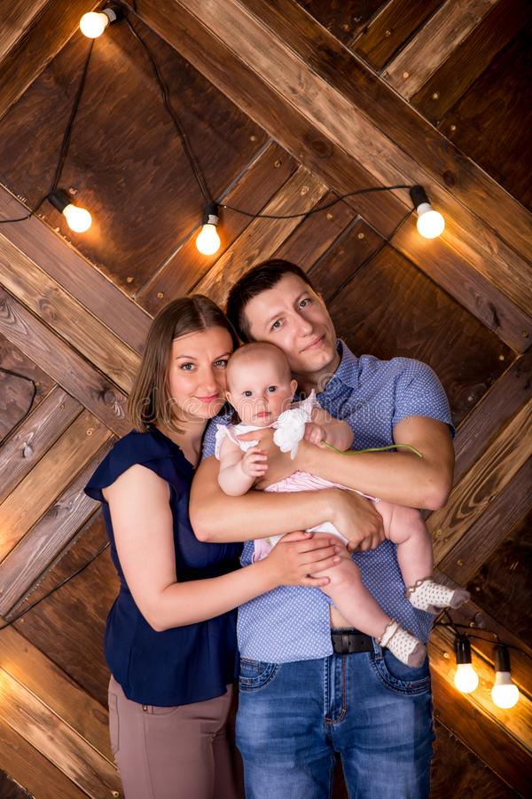 Jeune famille caucasienne heureuse posant dans le studio photographie stock