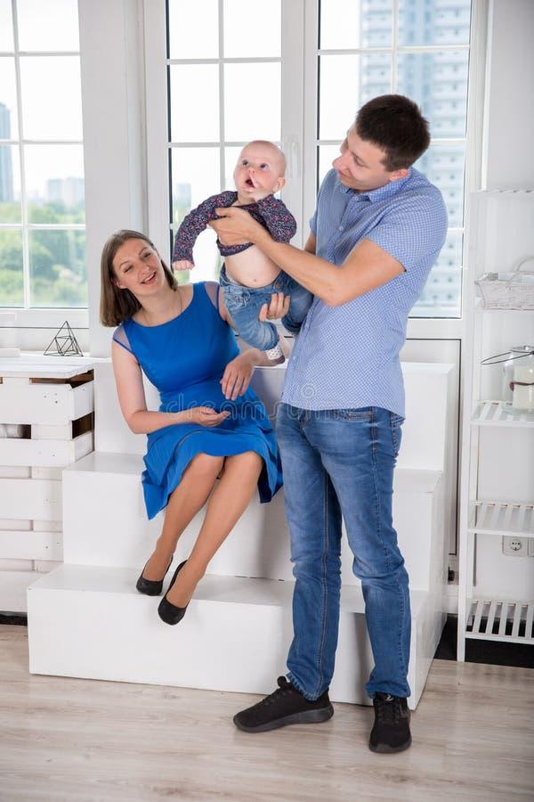 Jeune famille caucasienne heureuse posant dans le studio image stock