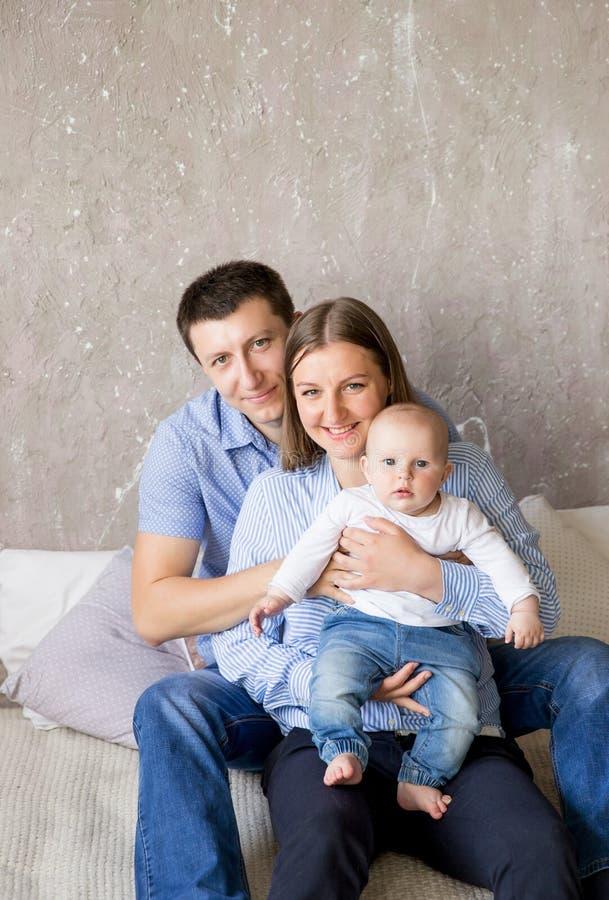 Jeune famille caucasienne heureuse s'asseyant sur le lit photos stock