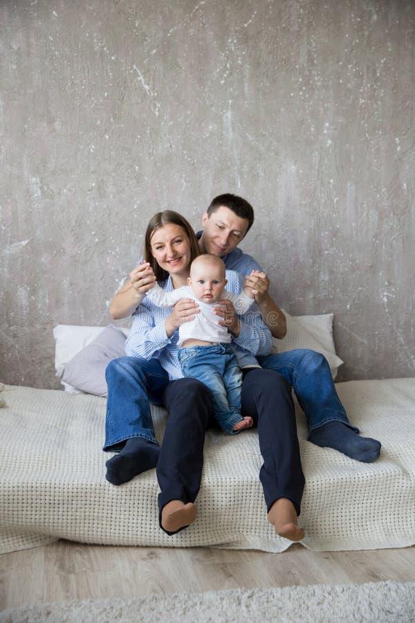 Jeune famille caucasienne heureuse s'asseyant sur le lit photographie stock libre de droits