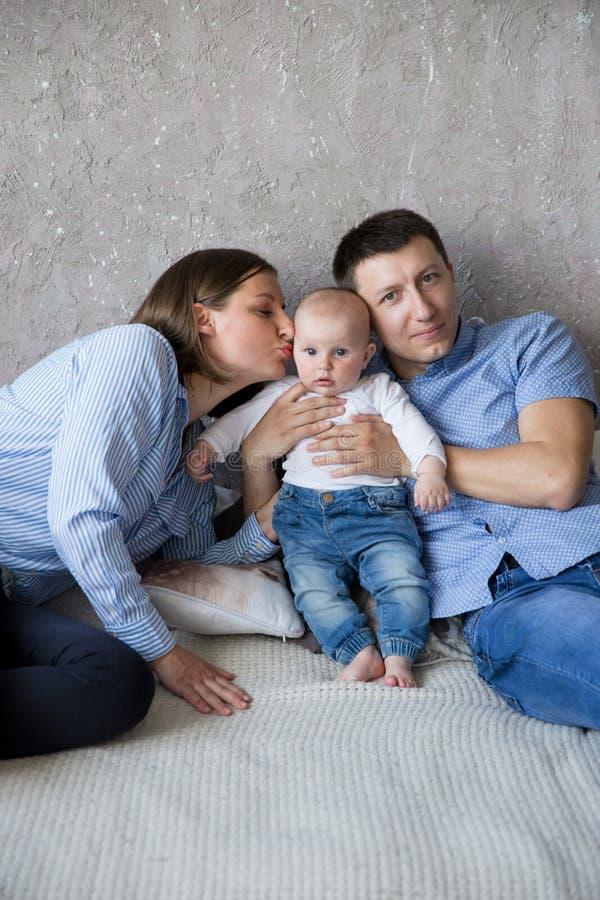 Jeune famille caucasienne heureuse se trouvant sur le lit photos libres de droits