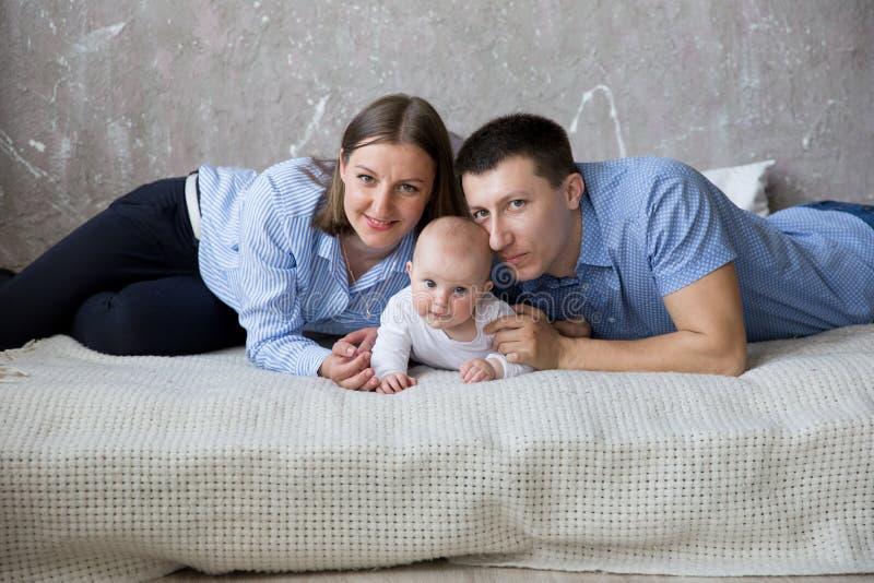 Jeune famille caucasienne heureuse se trouvant sur le lit photo stock