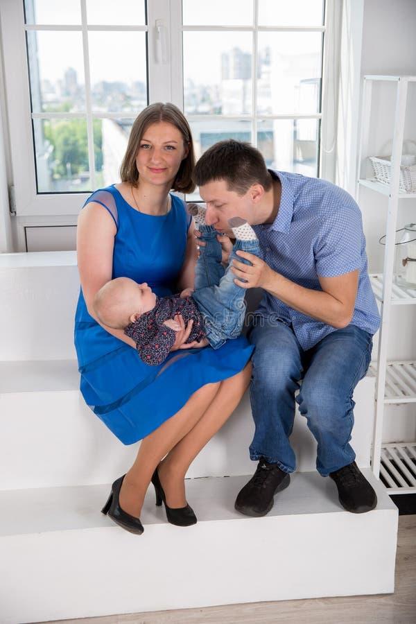 Jeune famille caucasienne heureuse sur l'escalier images stock