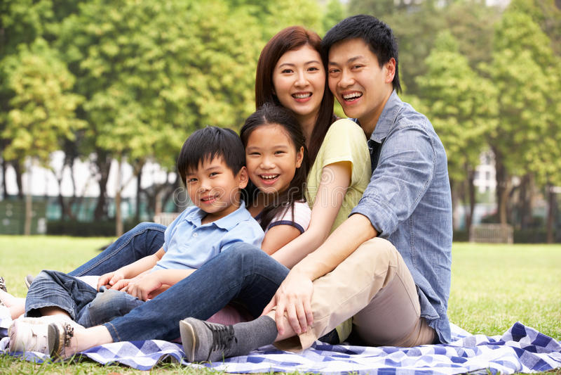 Jeune famille chinois détendant en stationnement ensemble photo libre de droits