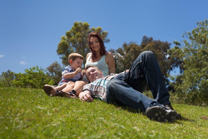 Jeune famille détendant dehors image stock