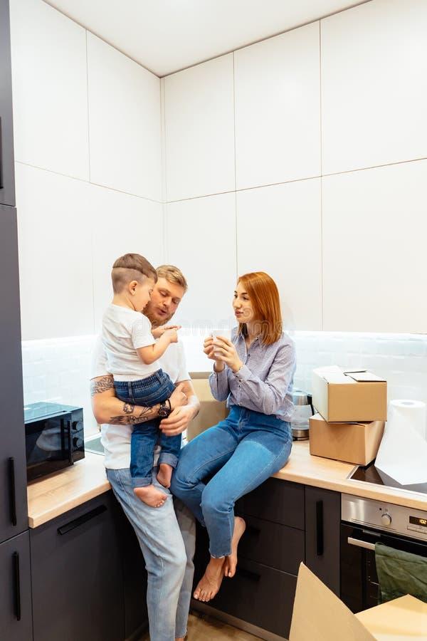 Jeune famille d?ballant des bo?tes dans la nouvelle maison photographie stock libre de droits