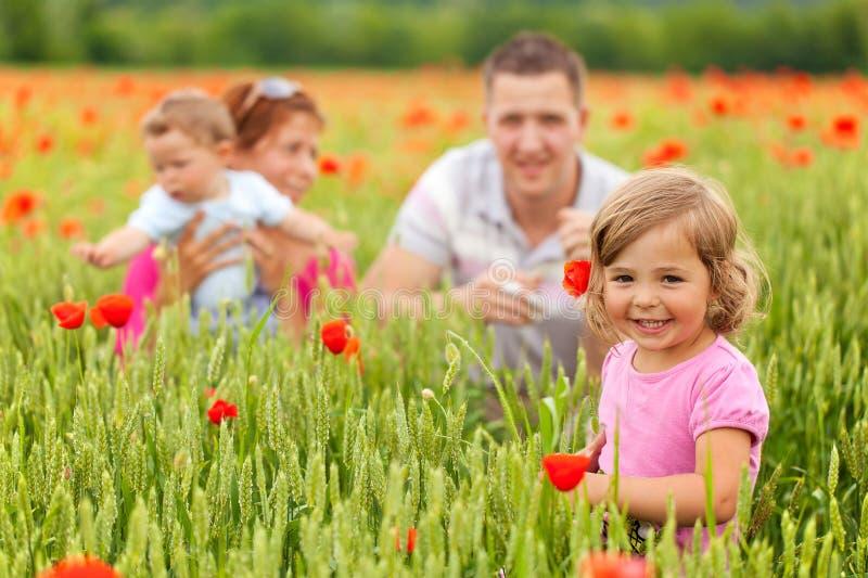Jeune famille dans le domaine de pavot photographie stock