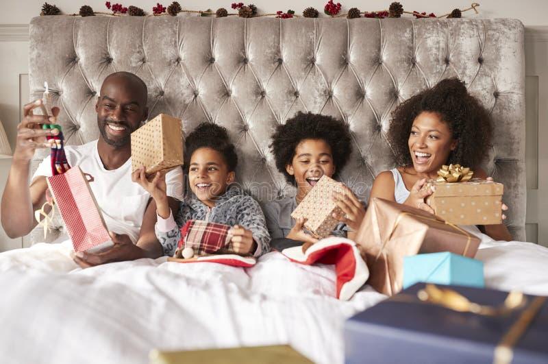 Jeune famille de métis se reposant dans le lit tenant ensemble des présents le matin de Noël, vue de face, fin  photographie stock