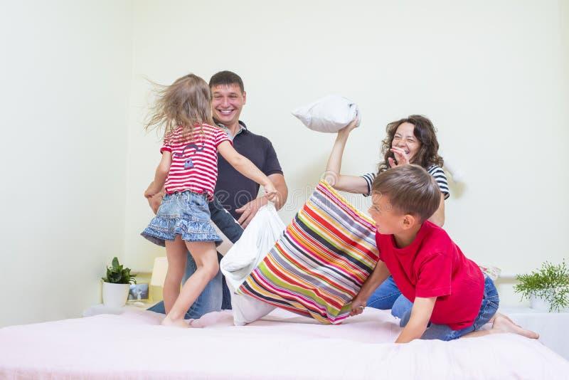 Jeune famille de quatre caucasienne ayant un combat d'oreiller drôle espiègle sur le lit à l'intérieur images stock