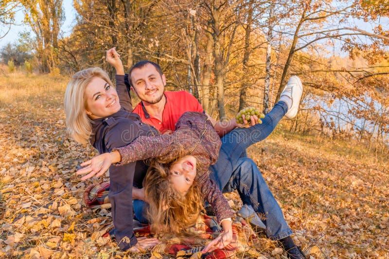 Jeune famille de sourire s'asseyant sur l'herbe d'automne et ayant l'amusement image stock