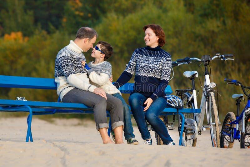 Jeune famille de trois ayant le repos sur le banc pendant leur équitation de vélo sur la plage photo stock