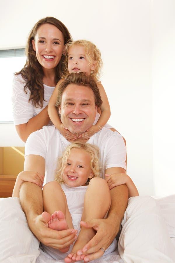 Jeune famille gaie dans le lit à la maison photographie stock