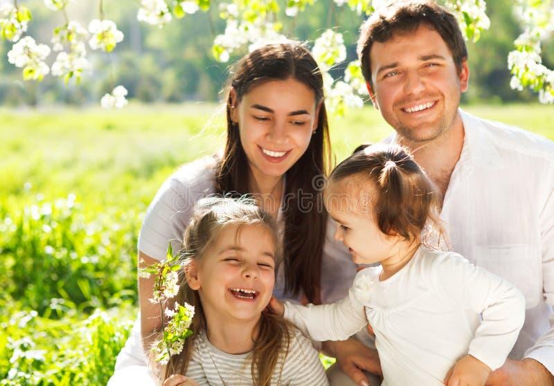 Jeune famille heureuse avec deux enfants dehors photographie stock libre de droits