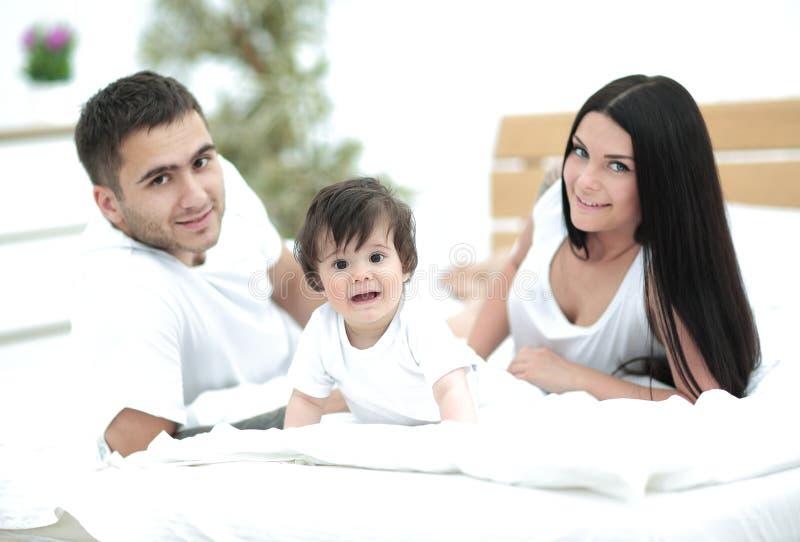 Jeune famille heureuse avec un bébé se situant dans le lit et le sourire photographie stock libre de droits