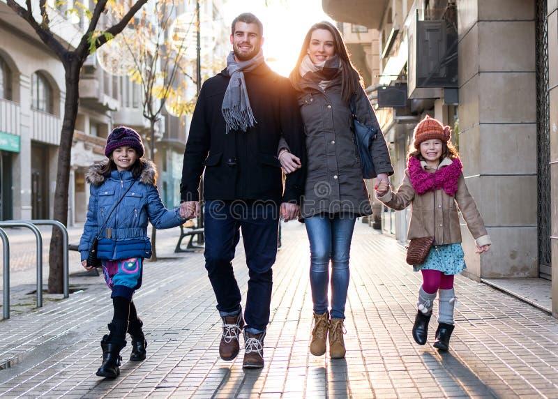 Jeune famille heureuse ayant l'amusement dans la rue image stock