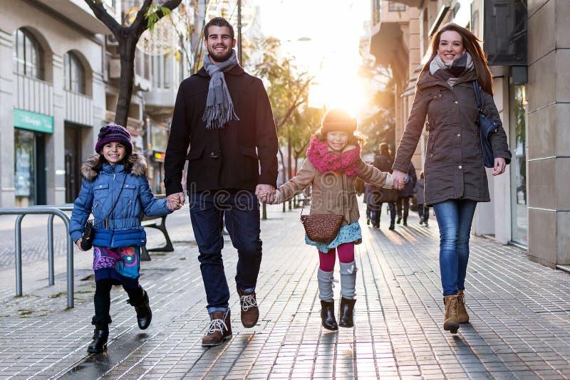 Jeune famille heureuse ayant l'amusement dans la rue photographie stock libre de droits