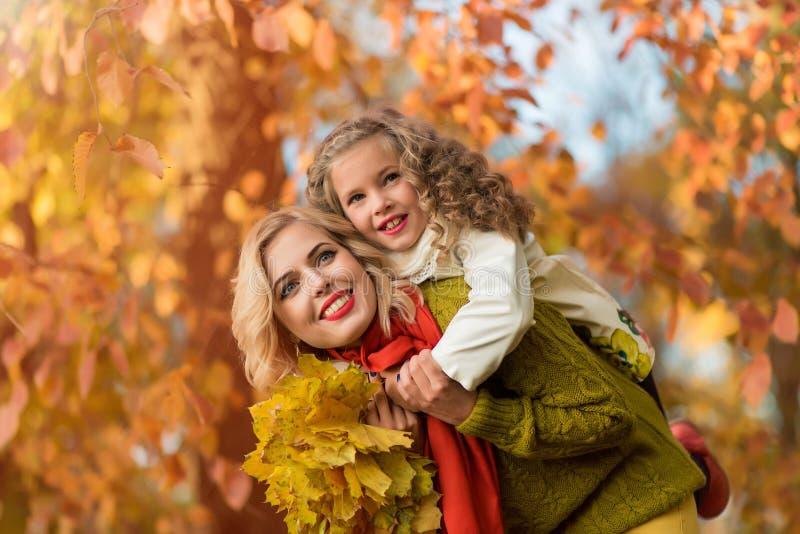 Jeune famille heureuse ayant l'amusement dans le parc d'automne photo libre de droits