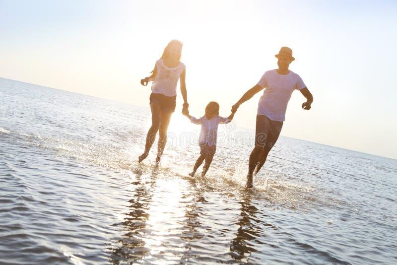 Jeune famille heureuse ayant l'amusement fonctionnant sur la plage au coucher du soleil image stock