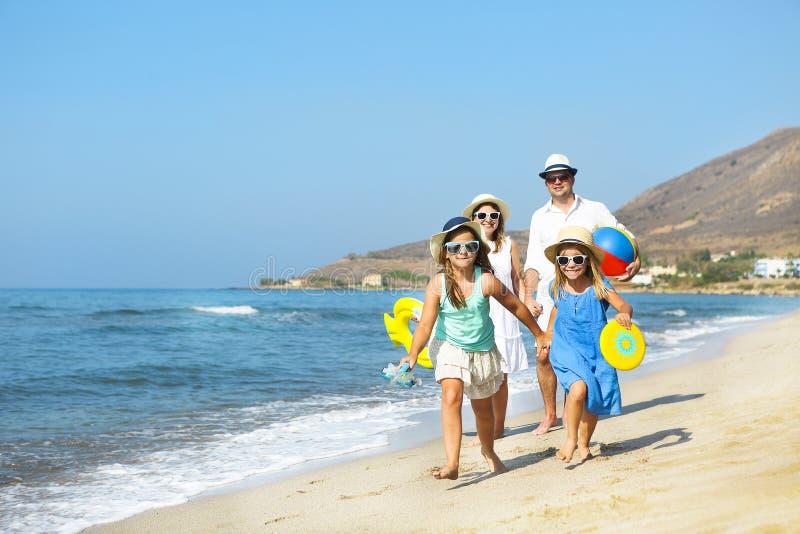 Jeune famille heureuse ayant l'amusement fonctionnant sur la plage au coucher du soleil famille images stock