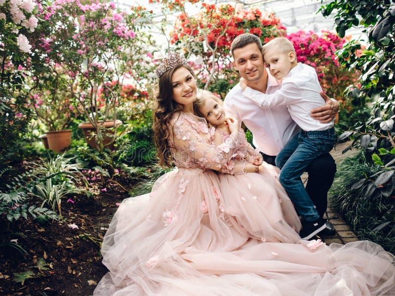 Jeune famille heureuse dans un jardin de floraison de ressort photographie stock