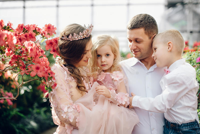 Jeune famille heureuse dans un jardin de floraison de ressort image stock