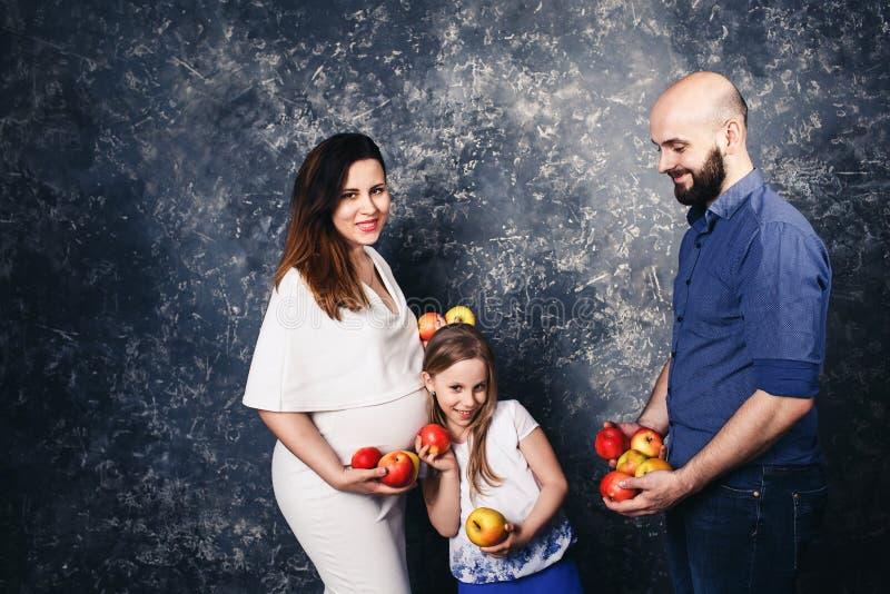 Jeune famille heureuse de vegan la mère enceinte, le père barbu, et peu de fille tiennent des pommes dans leurs mains et sourire photos stock