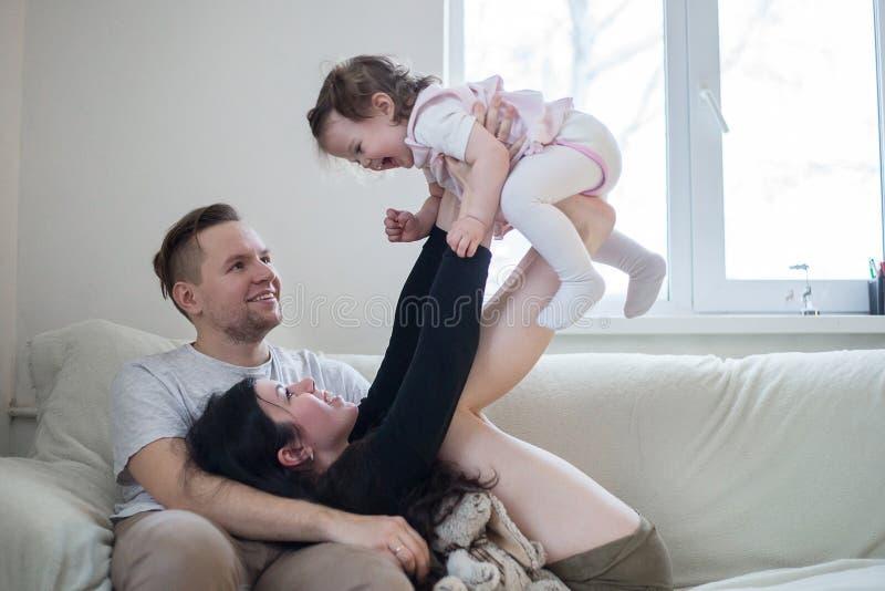 Jeune famille heureuse du jeu trois avec la fille photos libres de droits