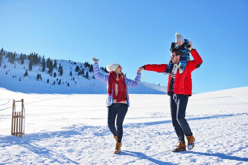 Jeune famille heureuse jouant dans la neige fraîche au beau jour d'hiver ensoleillé extérieur en nature image stock