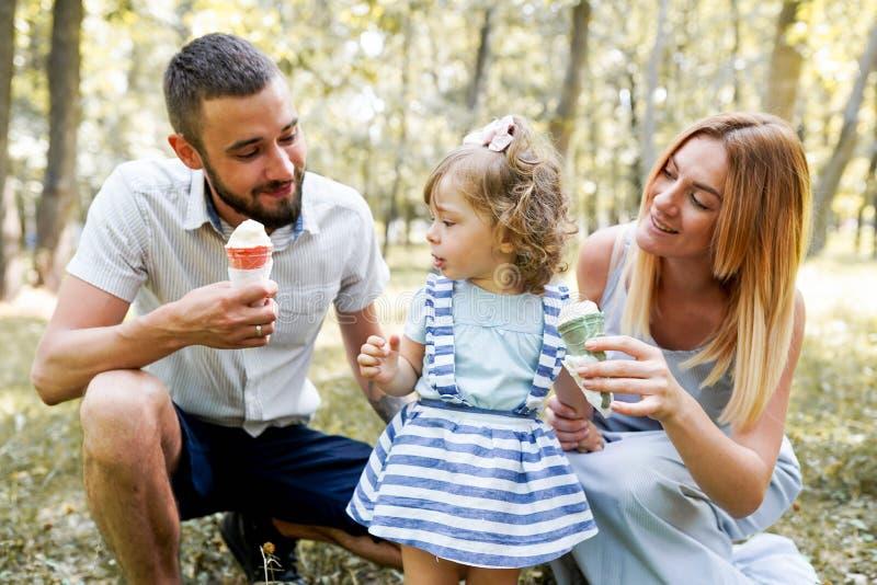 Jeune famille heureuse mangeant la crème glacée, passant le temps ensemble extérieur en parc naturel vert Parents, enfance, enfan image stock