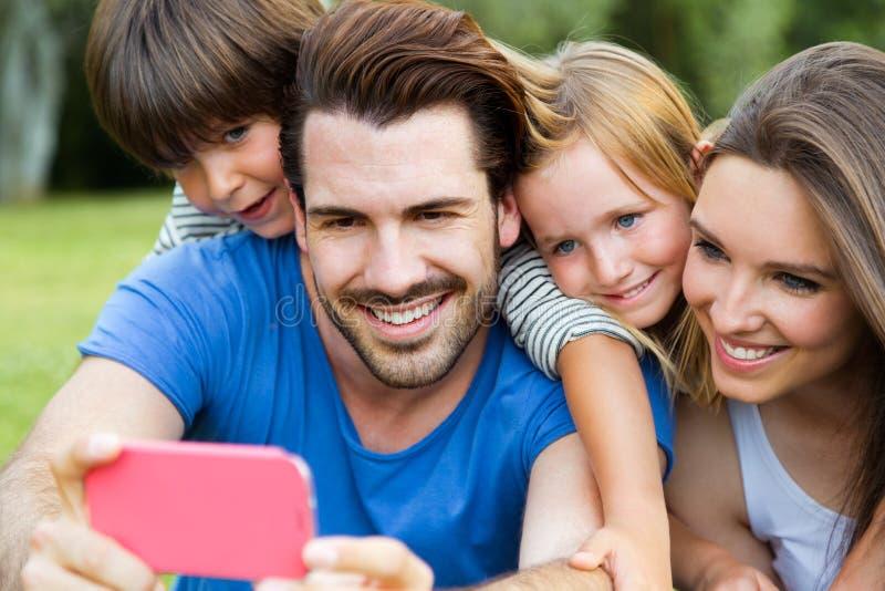Jeune famille heureuse prenant des selfies avec son smartphone dans le pair image stock