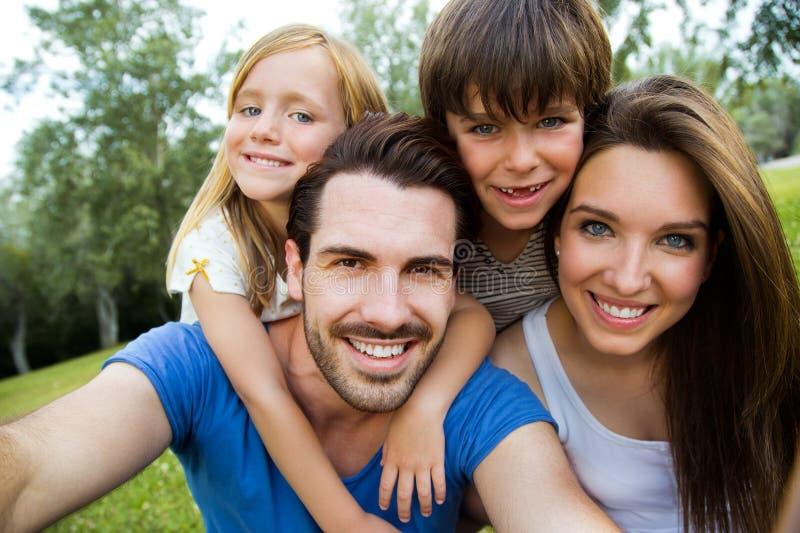 Jeune famille heureuse prenant des selfies avec son smartphone dans le pair image libre de droits