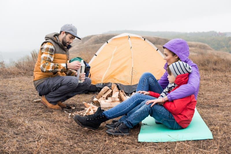 Jeune famille heureuse s'asseyant près de la tente photographie stock libre de droits