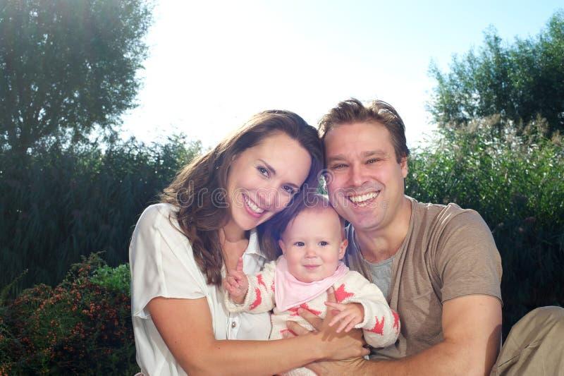 Jeune famille heureuse tenant le bébé mignon dehors photo stock