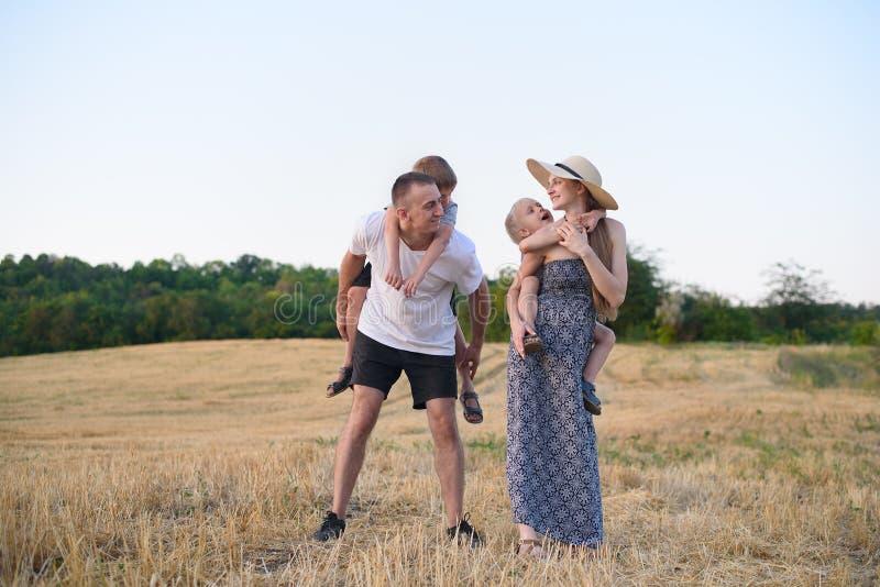 Jeune famille heureuse Un p?re, une m?re enceinte, et deux peu de fils sur leurs dos Champ de bl? biseaut? sur le fond Coucher du photo libre de droits