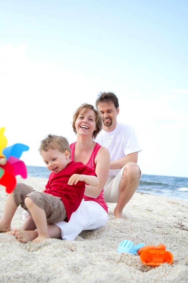 Jeune famille heureux sur la plage images stock