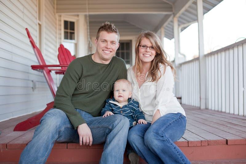 Jeune famille heureux sur le porche image libre de droits