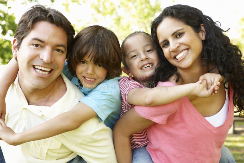 Jeune famille hispanique ayant le ferroutage dans le parc photo stock
