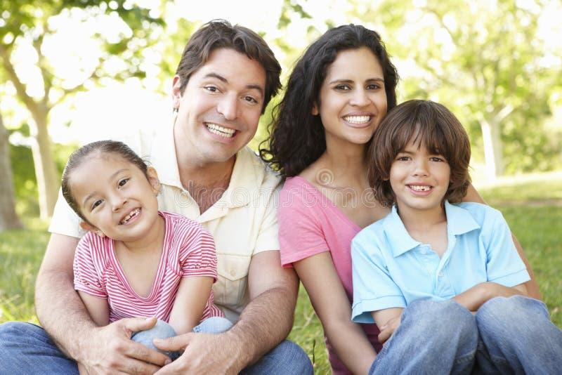 Jeune famille hispanique détendant en parc image stock