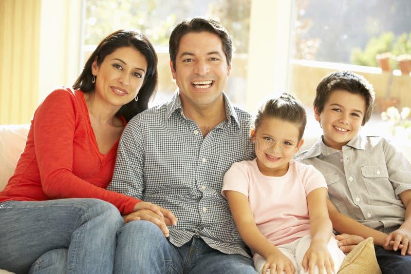 Jeune famille hispanique détendant sur Sofa At Home photos libres de droits