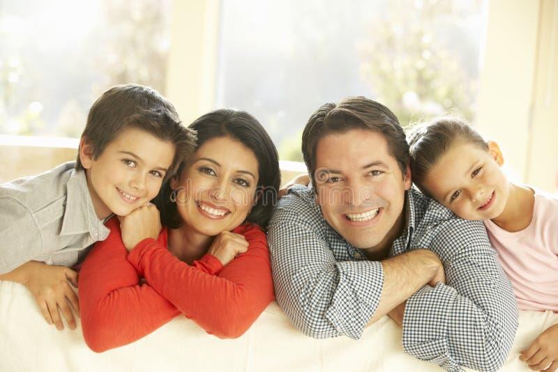 Jeune famille hispanique détendant sur Sofa At Home image stock