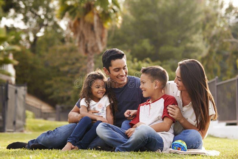 Jeune famille hispanique heureuse s'asseyant ensemble sur l'herbe en parc, regardant l'un l'autre image stock