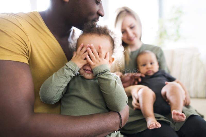 Jeune famille interraciale avec de petits enfants à la maison images stock