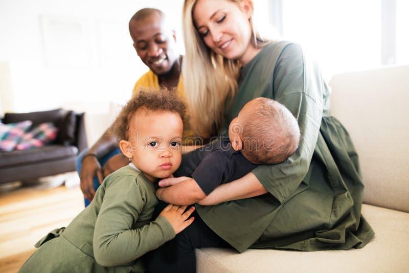 Jeune famille interraciale avec de petits enfants à la maison photographie stock