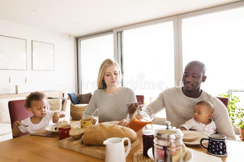 Jeune famille interraciale avec de petits enfants prenant le petit déjeuner photos stock