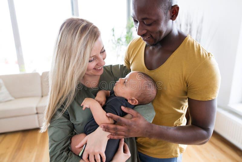 Jeune famille interraciale avec le petit fils de bébé à la maison photo stock