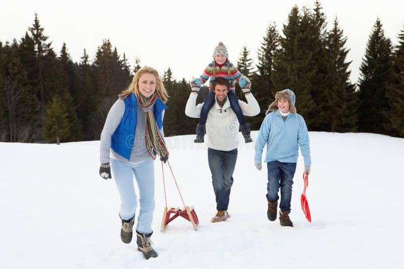 Jeune famille marchant par la neige avec le traîneau photographie stock libre de droits