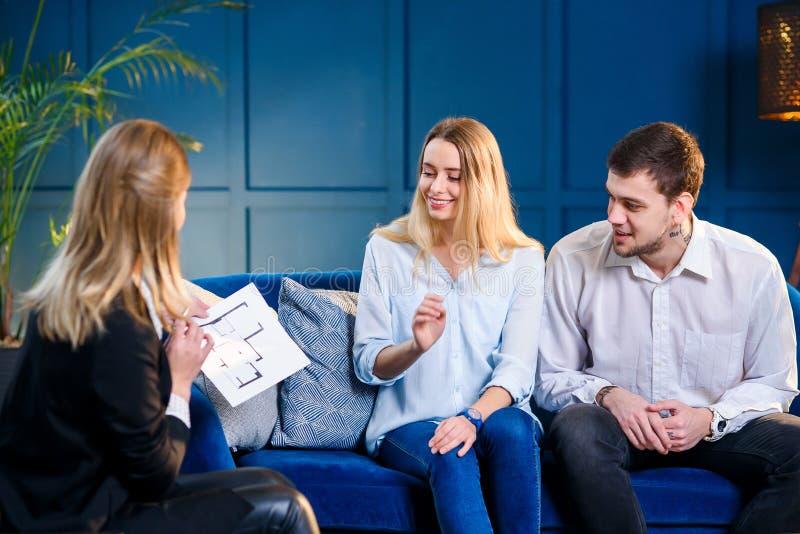 Jeune famille mignonne sur la réunion avec l'agent immobilier, dessinateur d'intérieurs, décorateur images stock